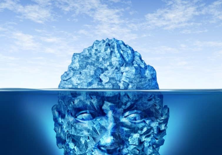 Exploration and discovery concept with an iceberg floating on a blue ocean and the underwater portion of the frozen ice is in the shape of a human head as a business and life symbol in searching for opportunities and dangers.