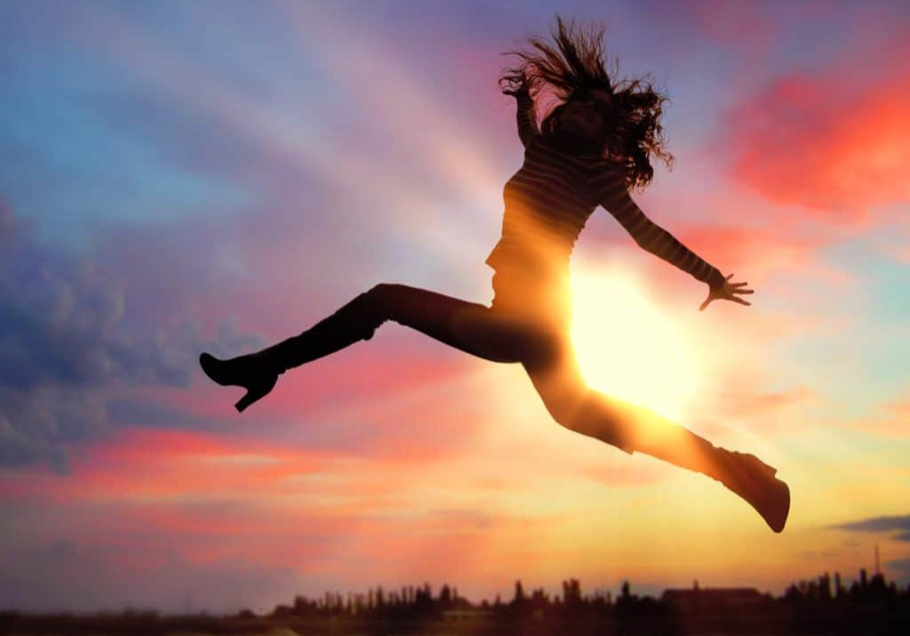 Silhouette of excited woman jumping at sunset