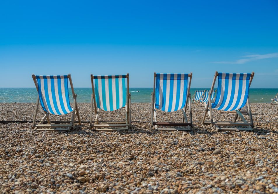4 blue and white deck chairs on a pebble beach.