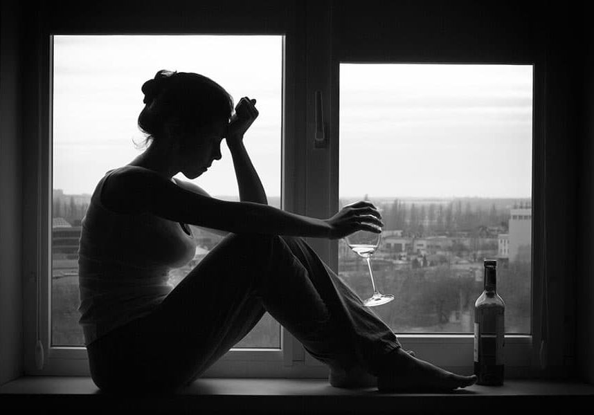 Sad young woman sitting on the window, drinks wine. Alcoholism problem. Black and white photography.