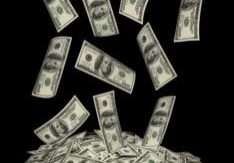 big pile of money. stack of american dollars on the black backgrounds