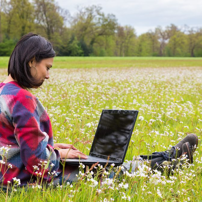 Colombian woman sitting with laptop in meadow with blooming flowers